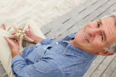 Starfish Holding des älteren Mannes Lizenzfreies Stockbild