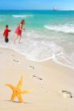 Starfish, kids and Footprints on Beach Stock Photos