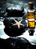 Starfish laying on a basalt stone and massage oils Royalty Free Stock Photography