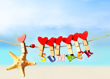 Starfish with letters and hearts hanging from clothespins Royalty Free Stock Photo
