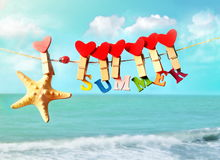 Starfish with letters and hearts hanging from clothespins. On summer beach Stock Images
