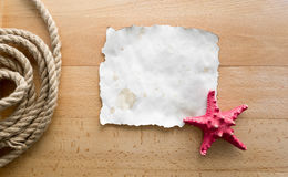 Starfish lying on blank piece of paper over wooden boards Stock Photo