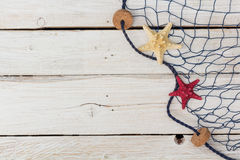 Starfish, marine network and rope on the old board Stock Image