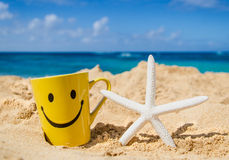 Starfish with mug on the sandy beach Stock Photo