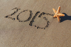 Starfish next to 2015 written on sand Stock Images