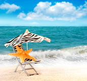 Starfish with parasol on sandy beach Royalty Free Stock Image