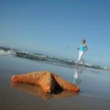 Starfish and running woman on the beach Stock Image