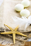 Starfish on sacking. Starfish on sackcloth with candles and feathers Stock Image
