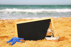 Starfish, sailboat and chalkboard, on sea sand and ocean horizon Stock Image