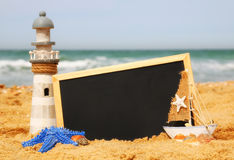 Starfish, sailboat, lighthouse and chalkboard, on sea sand and ocean horizon Stock Photo
