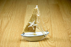 Starfish on sailboat. Toy with wood background Royalty Free Stock Photography