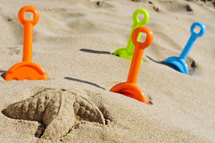 Starfish sand and toy shovels of different colors on the sand Royalty Free Stock Photos
