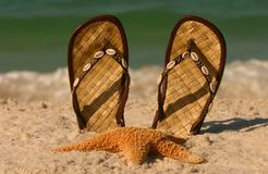 Starfish and Sandals. A starfish and shell trimmed sandals set against the incoming foamy ocean surf.  Shot with shallow DOF Stock Photography