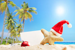 Starfish with Santa hat and banner on a beach Stock Photos