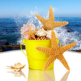 Starfish & Sea Shells In Yellow Beach Bucket. Day Spa Still-life With Starfish And Sea Shells In Colorful Yellow Beach Bucket On White Glass Table Royalty Free Stock Image