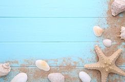 Starfish and seashells with sand on a wooden background. Summer concept stock image