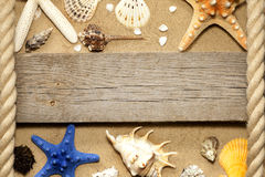 Starfish and shells on beach with empty board Royalty Free Stock Photos