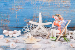 Starfish and shells with figurine in deck chair for summer, holi Royalty Free Stock Image