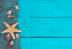 Starfish and shells in fish netting on teal blue wood sign. Blank antique teal blue aged wood sign background with fish net border full of seashells and two Royalty Free Stock Image