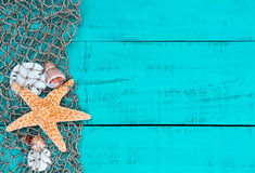 Starfish and shells in fish netting on teal blue wood sign Stock Images
