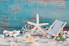 Starfish and shells with toy deck chair and a wooden turquoise b Stock Photography