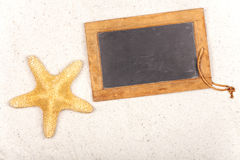 Starfish and Slate Blackboard in the Sand Royalty Free Stock Images