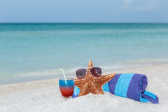 Starfish standing on white sand beach on tranquil ocean background. Starfish standing on white sand beach between towel and colorful cocktail in wine glass royalty free stock photography