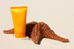 Starfish and sun protection tube on sand Royalty Free Stock Photography