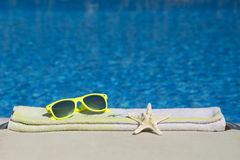 Starfish, sunglasses and towel on the sunbed next to the swimming pool Royalty Free Stock Image