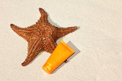 Starfish and suntan tube on sand Stock Photos