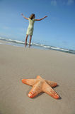 Starfish and tranquil girl on the beach Stock Photo