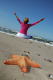 Starfish and tranquil woman on the beach Royalty Free Stock Photos