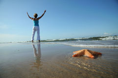 Starfish and tranquil woman on the beach Royalty Free Stock Photo