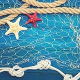 Starfish und Muschel auf einem blauen hölzernen Hintergrund Lizenzfreies Stockbild