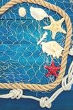 Starfish und Muschel auf einem blauen hölzernen Hintergrund Lizenzfreies Stockfoto