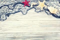 Starfish und Muschel auf einem hellen hölzernen Hintergrund Stockfotografie