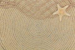 Starfish- und Seenetz liegen auf dem Hintergrund, der vom Seil gemacht wird Stockbild