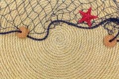 Starfish- und Seenetz liegen auf dem Hintergrund, der vom Seil gemacht wird Lizenzfreie Stockbilder
