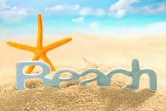 Starfish und Zeichen für Strand im Meersand Lizenzfreie Stockfotos