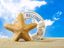 Starfish and welcome sign on beach Stock Photo
