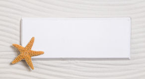 Starfish on a white sign in a sand background for summer Stock Image