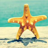 Starfish on wooden pier and text happy summer Royalty Free Stock Photography