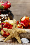 Starfish on wooden table. Beautiful red roses in the background Stock Photography
