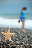 Starfish and young girl on stone seacoast Royalty Free Stock Photos