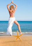 Starfish and young woman at the beach Stock Photos