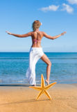 Starfish and young woman at the beach Royalty Free Stock Images
