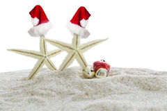 Starfishes with christmas hats on sand. Christmas vacation concept. Two starfishes with red christmas hats and two christmas bells on the white beach sand stock photography