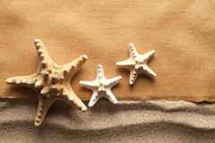Starfishes and handmade paper sheet on beach Royalty Free Stock Images