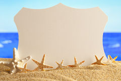 Starfishes and paper card on the beach Stock Image
