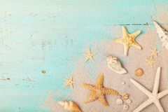 Starfishes and seashells on sand for summer holidays and travel background royalty free stock image